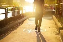 Caminhada da mulher do esporte na pista da bicicleta do símbolo no nascer do sol vibrante, foco macio Imagens de Stock