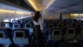 A caminhada da mulher do passageiro no corredor do avião, sai do avião de passageiros boing filme