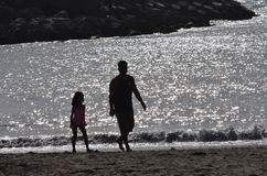 Caminhada da praia do pai e da filha foto de stock