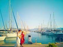 Caminhada de duas mulheres ao longo do porto do iate Fotos de Stock Royalty Free