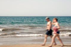 Caminhada do homem e da mulher ao longo da praia Fotos de Stock