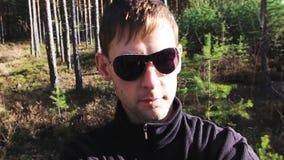 Caminhada do homem novo na floresta com óculos de sol, película do auto a enfrentar video estoque