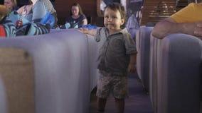Caminhada do rapaz pequeno entre o sofá no restaurante Evento das crianças celebration Povos vídeos de arquivo