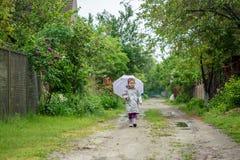 Caminhada do verão na menina da chuva com um guarda-chuva Imagens de Stock Royalty Free