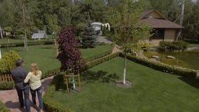 Caminhada dos pares de Adulrt no jardim verde vídeos de arquivo