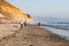 Caminhada dos povos ao longo do por do sol de Torrey Pines State Beach Near fotografia de stock
