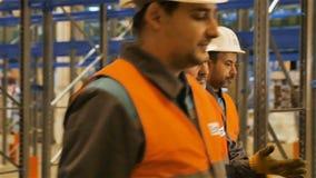 Caminhada dos trabalhadores do movimento lento ao longo do depósito com prateleiras montadas video estoque