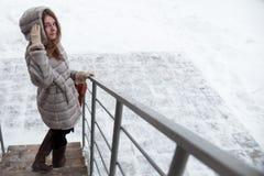 Caminhada em torno da cidade: a menina girou para trás e olhado a câmera, vindo em baixo Fotografia de Stock Royalty Free