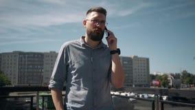 A caminhada farpada nova considerável do homem e fala no telefone na cidade vídeos de arquivo