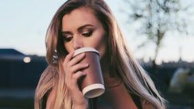 A caminhada longa longa do cabelo da mulher 'sexy' bonita no parque da cidade na xícara de café grande da bebida da cidade relaxa filme