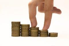 Caminhada masculina dos dedos em escadas das moedas Foto de Stock