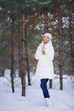 Caminhada modelo nova da menina na floresta do inverno Foto de Stock
