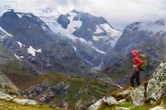 Caminhada - mulher do caminhante no passeio na montanha com a trouxa na chuva Foto de Stock