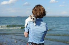 Caminhada pelo mar com animal de estimação doméstico Menina que guarda um gato branco Fundo do mar e da ilha no dia ensolarado imagem de stock royalty free