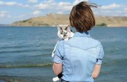 Caminhada pelo mar com animal de estimação doméstico Menina que guarda um gato branco Fundo do mar e da ilha no dia ensolarado foto de stock