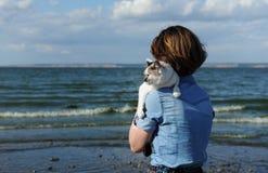 Caminhada pelo mar com animal de estimação doméstico Menina que guarda um gato branco Fundo do mar e da ilha no dia ensolarado imagens de stock royalty free