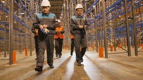 Caminhada profissional dos trabalhadores do movimento lento entre prateleiras altas filme