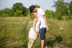 Caminhada romântica nova dos pares no campo pelas mãos e para rir na primavera Pares no ar livre de passeio branco que guarda o s imagens de stock royalty free