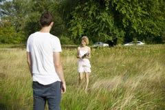Caminhada romântica nova dos pares no campo pelas mãos e para rir na primavera Pares no ar livre de passeio branco que guarda o s fotografia de stock royalty free