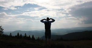 Caminhada só nas montanhas O homem com uma trouxa está antes de uma paisagem bonita da montanha e estica sob o azul video estoque