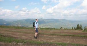 Caminhada só nas montanhas O homem novo considerável anda ao longo do monte com uma trouxa em seus ombros e olha ao redor filme