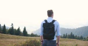 Caminhada só nas montanhas O homem novo considerável está com uma trouxa na parte superior de um monte e olha o thoughtfull em filme