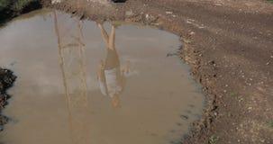 Caminhada só nas montanhas Reflecion de um turista masculino em uma água suja na associação filme