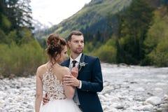 Caminhada Wedding A caminhada dos noivos ao longo do banco de rio, guardando-se mãos do ` s Retrato da noiva e do noivo imagem de stock