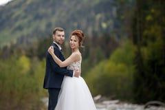 Caminhada Wedding A caminhada dos noivos ao longo do banco de rio, guardando-se mãos do ` s Retrato da noiva e do noivo imagem de stock royalty free