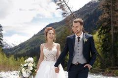 Caminhada Wedding A caminhada dos noivos ao longo do banco de rio, guardando-se mãos do ` s Retrato da noiva e do noivo foto de stock royalty free