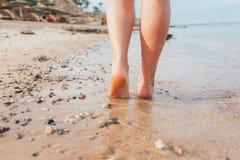 Caminhadas bonitas dos pés da menina na areia e na água do mar na praia foto de stock royalty free