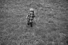 Caminhadas da criança Menino pequeno na grama verde Foto de Stock Royalty Free