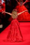 Caminhadas de Thalia do cantor a pista de decolagem no vermelho ir para a coleção vermelha 2015 do vestido das mulheres Foto de Stock Royalty Free