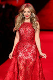 Caminhadas de Thalia do cantor a pista de decolagem no vermelho ir para a coleção vermelha 2015 do vestido das mulheres Imagem de Stock Royalty Free