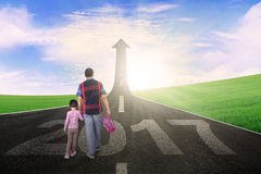 Caminhadas do homem e da menina na rua com 2017 Imagem de Stock