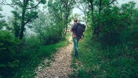 Caminhadas do viajante do homem ao longo de um trajeto com um estilo de vida do curso da floresta da montanha Fotografia de Stock