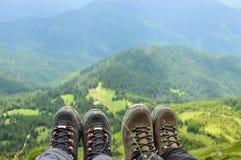 Caminhando as botas do viajante que sentam-se na montanha alta cobrem Fotos de Stock