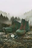 Caminhando botas com faca e compasso no log da árvore Imagem de Stock Royalty Free