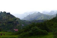 Caminhando em Thorsmörk - panorama da montanha com dois caminhantes e uma cabana com bandeira islandêsa, Islândia fotografia de stock royalty free