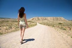 Caminhando a estrada do deserto Imagens de Stock Royalty Free