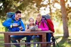 Caminhando a família para relaxar o assento e olhar no mapa imagens de stock royalty free