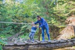 Caminhando a família que cruza uma ponte de madeira Fotos de Stock Royalty Free