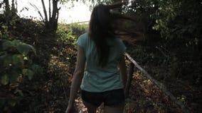 Caminhando a mulher que trekking na selva da floresta úmida Eleve a opinião traseira o caminhante fêmea novo que anda no passeio  filme