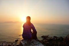 Caminhando a mulher sente-se no beira-mar do nascer do sol fotografia de stock royalty free