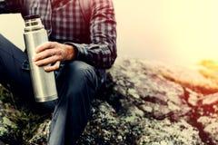 Caminhando o conceito do turismo da aventura O homem irreconhecível do caminhante que guarda a garrafa térmica em sua mão, close- fotos de stock royalty free