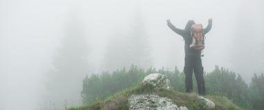 Caminhando o homem com os braços abertos da trouxa no pico de montanha nevoento fotos de stock royalty free