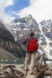 Caminhando o homem que olham o lago moraine & o Rocky Mountains Fotos de Stock Royalty Free