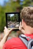 Caminhando o homem que toma imagens da natureza na tabuleta imagem de stock royalty free