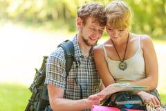 Caminhando o mapa backpacking da leitura dos pares na viagem foto de stock
