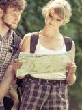 Caminhando o mapa backpacking da leitura dos pares na viagem Imagens de Stock